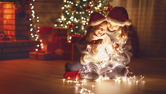 868220646 istock photo Merry Christmas! mother and child daughter with glowing garland near tree 876828410