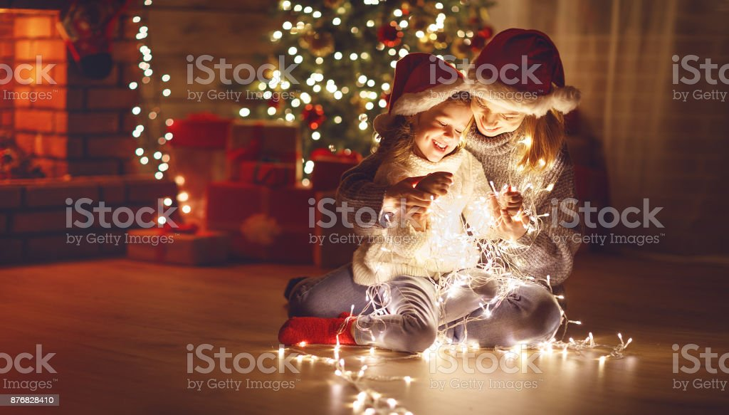 Merry Christmas! mother and child daughter with glowing garland near tree stock photo