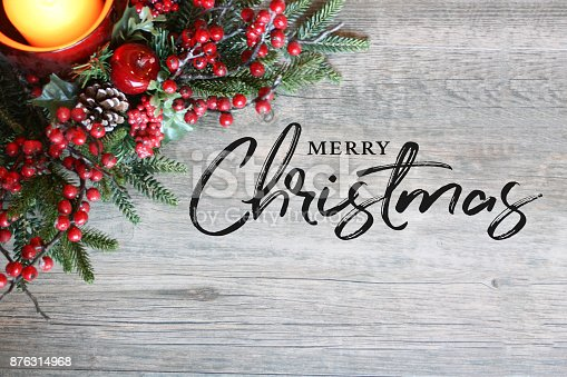 istock Merry Christmas Text, Candle, Pine Tree Branches and Berries in Top Corner Over Rustic Wood 876314968