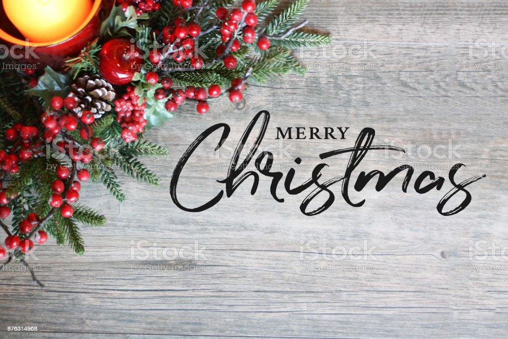 Texto de feliz Navidad, vela, ramas de pino y las bayas en la parte superior en madera rústica - foto de stock