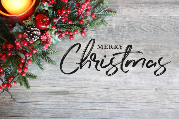 merry christmas text, candle, pine tree branches and berries in top corner over rustic wood - christmas stock photos and pictures