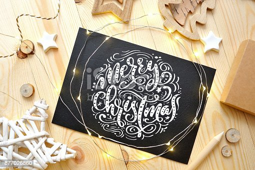 istock Merry Christmas text on a chalkboard with christmas deoccrusties star, garland on wooden background. Photography for holiday greeting card, invitation, calendar poster banner 877026860