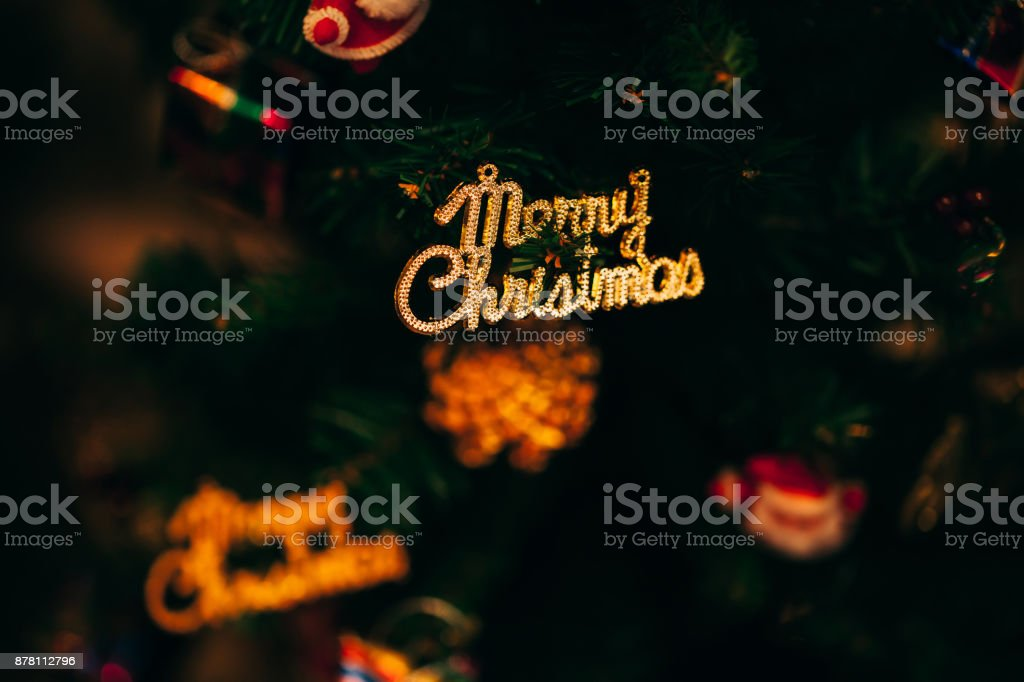 Merry Christmas text sign ornament attached on Xmas tree - selective focus. stock photo