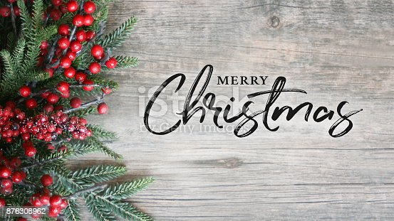 istock Merry Christmas Text with Holiday Evergreen Branches and Berries Over Rustic Wooden Background 876308962