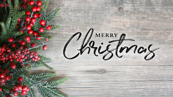 Merry Christmas Text with Holiday Evergreen Branches and Berries Over Rustic Wooden Background