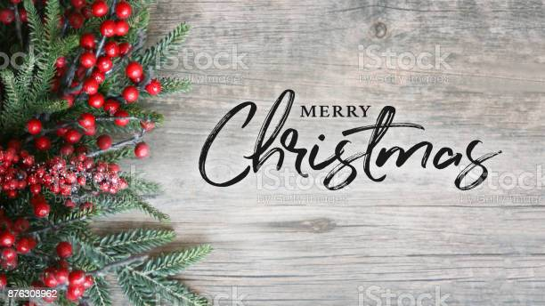 Merry christmas text with holiday evergreen branches and berries over picture id876308962?b=1&k=6&m=876308962&s=612x612&h=cgis annxo9kq2x3vrbhffdrukemskt6w uogdoo6j8=