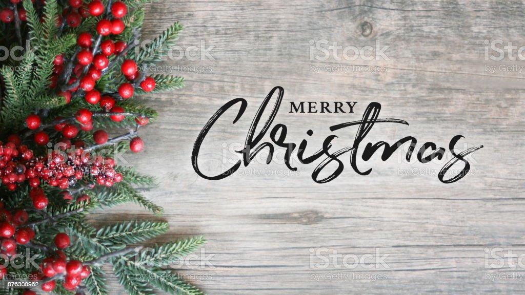 Texto de feliz Navidad con árbol de hoja perenne vacaciones ramas y bayas sobre fondo de madera rústico - foto de stock