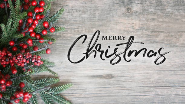 Merry Christmas Text with Holiday Evergreen Branches and Berries Over Rustic Wooden Background stock photo