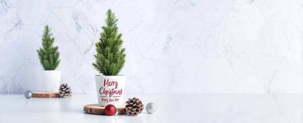 Merry christmas tree with pine cone,decor red xmas ball on wood log at white table and marble tile wall background.clean minimal simple style.holiday still life with space to adding text stock photo
