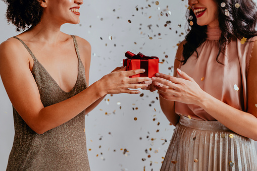 Hands of an unrecognizable smiling young woman holding a red gift