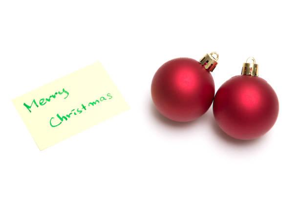 Merry christmas writen on yellow sheet and christmas ball on white background stock photo
