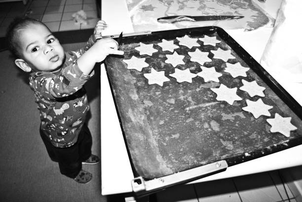 merry christmas : young child taking a gingerbread cookie. black and white - santa claus tiptoeing foto e immagini stock
