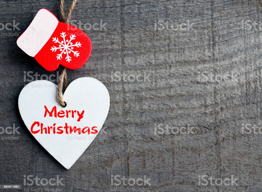 Merry Christmas.Decorative white wooden Christmas heart and red mitten on grey rustic wooden background.Winter holidays concept. stock photo