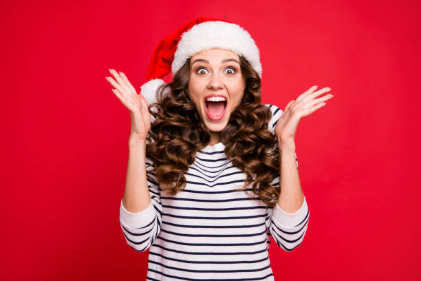 merry holly x mas portrait of crazy cool cheerful glad positive optimistic charming curly-haired girl in casual striped pullover clapping palms waiting for gift isolated over red background - santa hat stock pictures, royalty-free photos & images