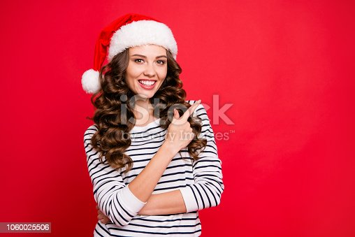 istock Merry holly x mas portrait of nice cheerful glad positive optimistic charming attractive curly-haired girl in casual striped pullover pointing aside copy blank empty space isolated over red background 1060025506