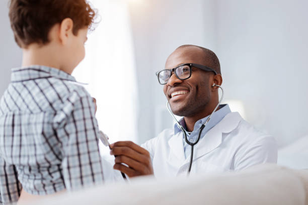 Merry male doctor performs boys examination stock photo