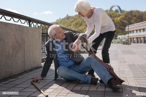 istock Merry pensioner sitting on the street and receiving help 684539332
