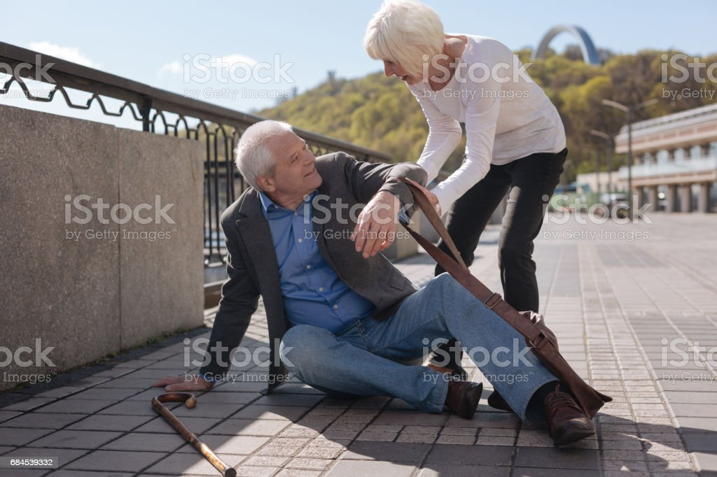 Merry pensioner sitting on the street and receiving help stock photo