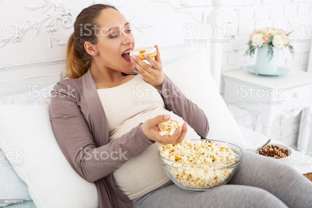 Merry pregnant woman biting French pastry royalty-free stock photo