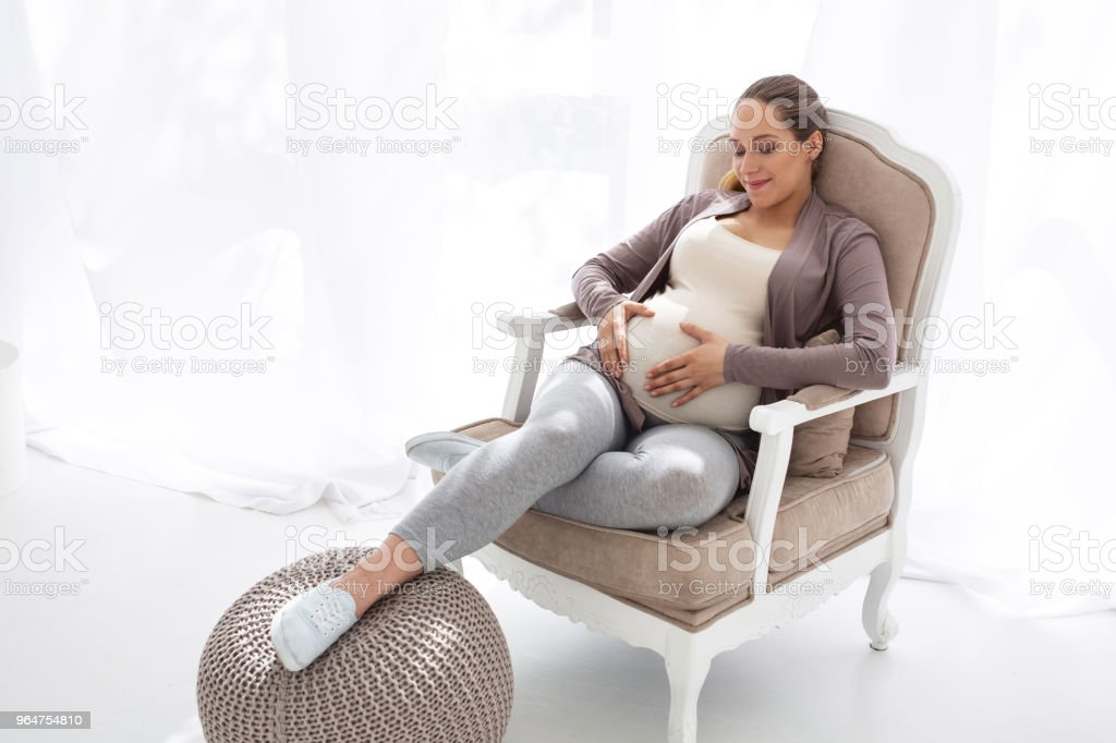 Merry pregnant woman hugging belly royalty-free stock photo