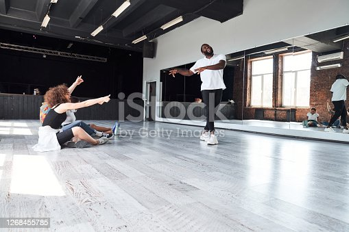 Happy males and females are visiting sport class for training hip-hop and guy is starting moving