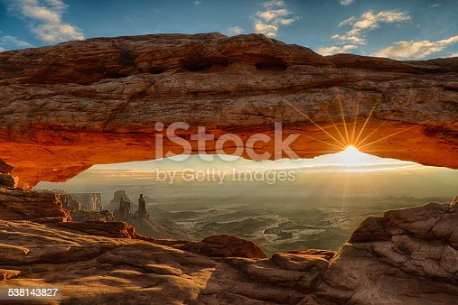 Sunburst under Mesa Arch, with the arches and landscape of Canyonlands National Park appearing under the arch