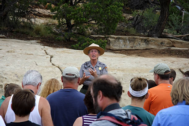 Mesa Verde Tour Group Mesa Verde National Park, CO - July 26, 2008: A park ranger speaks to a tour group prior to descending to the ancient Anasazi ruins of Cliff Palace in Mesa Verde National Park.  park ranger stock pictures, royalty-free photos & images