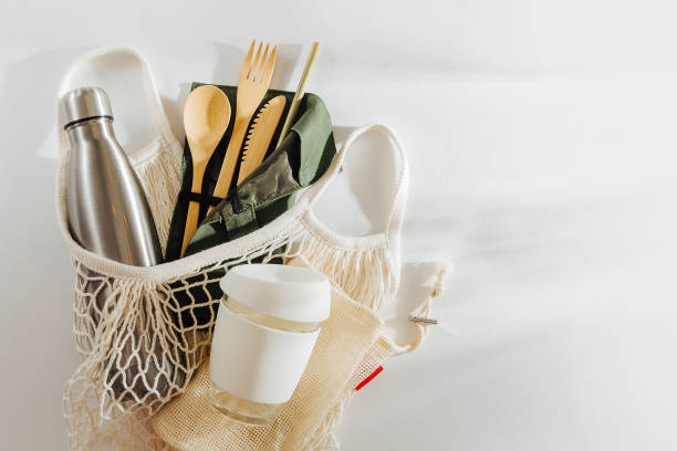 mesh market bag with bamboo cutlery, reusable coffee mug  and  water bottle. sustainable lifestyle.  plastic free concept. - riutilizzabile foto e immagini stock