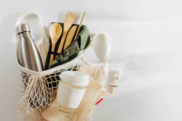mesh market bag with bamboo cutlery, reusable coffee mug  and  water bottle. sustainable lifestyle.  plastic free concept. - rifiuti zero foto e immagini stock
