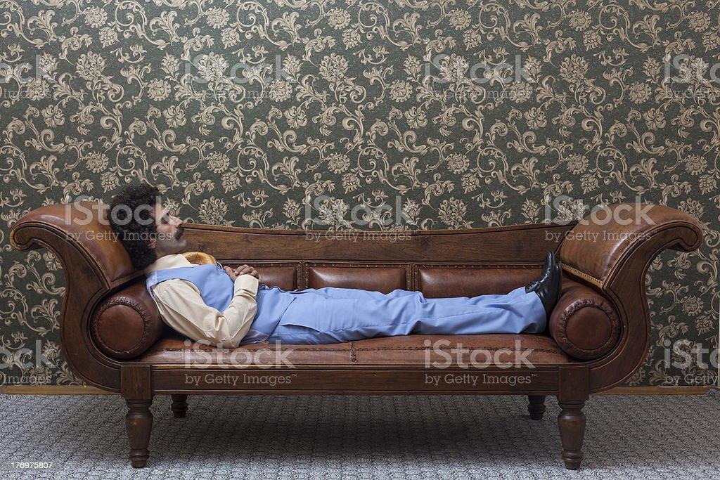 Mesmerized man lying down on coach in psychiatrist office royalty-free stock photo