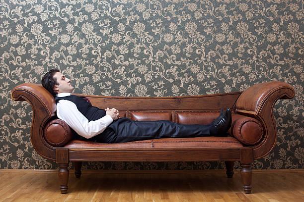 Mesmerized man lying down on coach in psychiatrist office stock photo