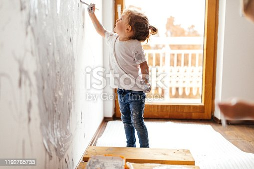 Kids making mess while using paint to renovate wall in their room