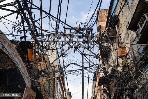 Delhi, India - December 14, 2019: Mess of electrical power line wires on the streets of Old Delhi
