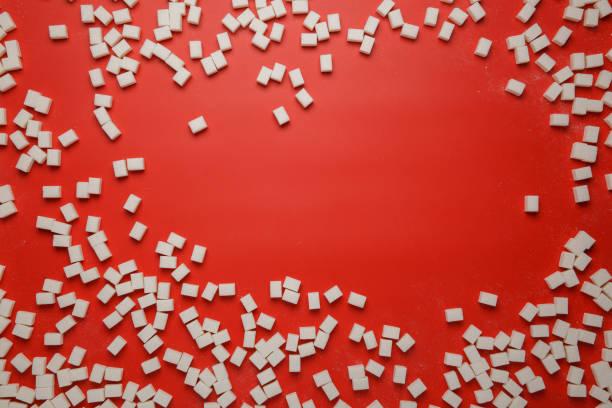 Durcheinander von Zuckerwürfeln auf rotem Hintergrund – Foto