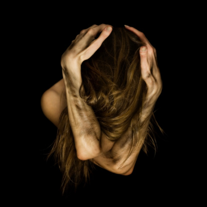woman holding head with crossed dirty hands looking down