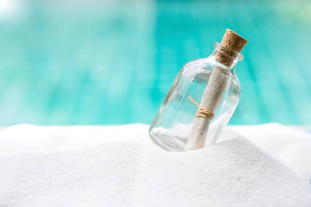 flasche auf weißem sand - sos einzelwort stock-fotos und bilder