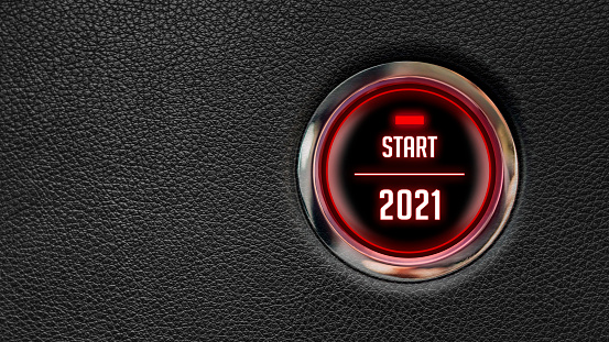 Red car engine start button about starting 2021 on black leather car dashboard background. Large copy space.