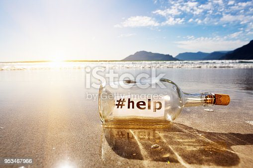 Bottle with a message asking for #help is washed up on a beautiful beach. The hashtag symbolizes social media.
