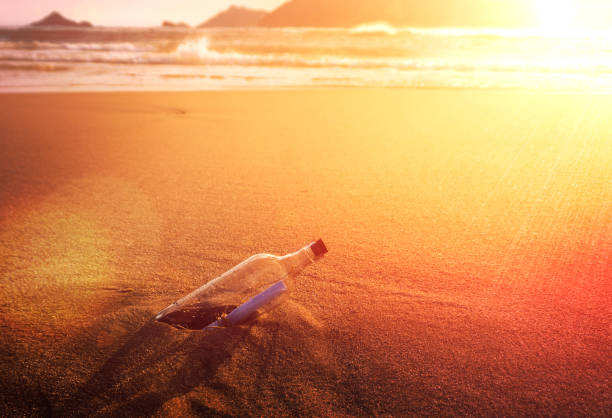 Message In A Bottle Glass Corked On Ocean Beach At Golden Sunset Conceptual stock photo