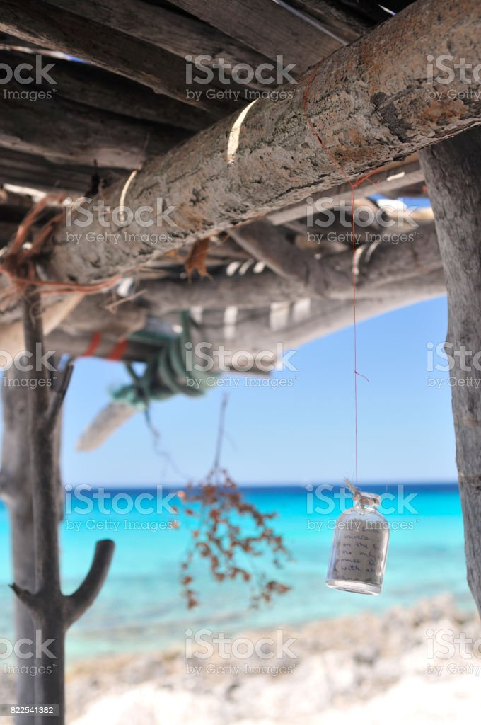 Message in a bottle hanging from the roof of wooden shelter on the coast. stock photo