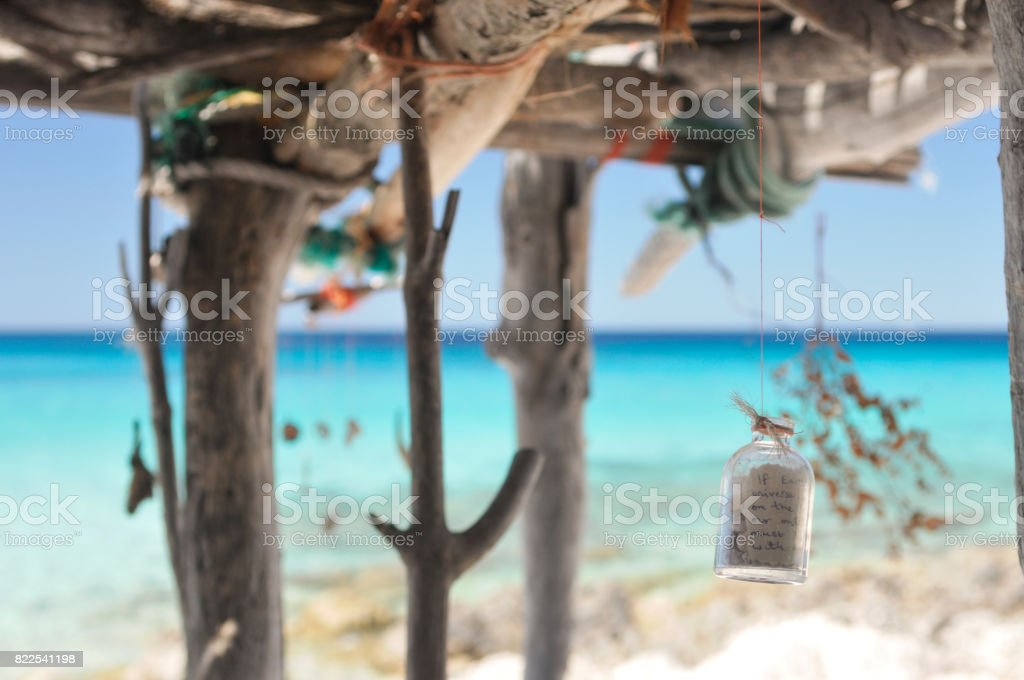 Message in a bottle in a wooden shelter on the beach stock photo