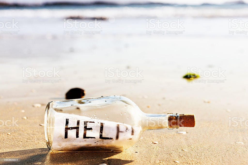 Message in a bottle on beach: Help! royalty-free stock photo
