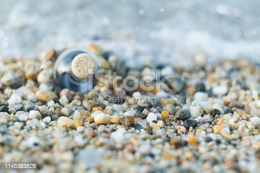 Close up shot of message in a bottle stuck in pebbles on a sea beach sand with out of focus waves visible in background.