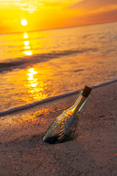 Message in a bottle, sunset tropical beach stock photo