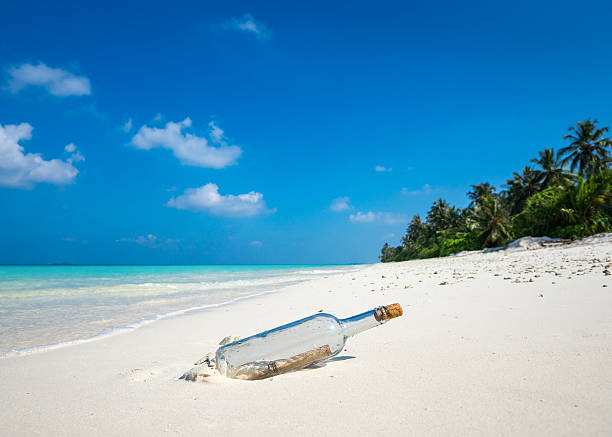 nachricht in einer flasche waschung an land auf einen tropischen strand. - rettungsinsel stock-fotos und bilder