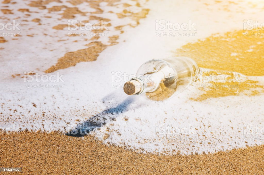Message in a bottle washed up by the sea stock photo