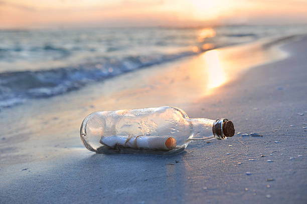 Message in a glass bottle on a beach at sunset stock photo