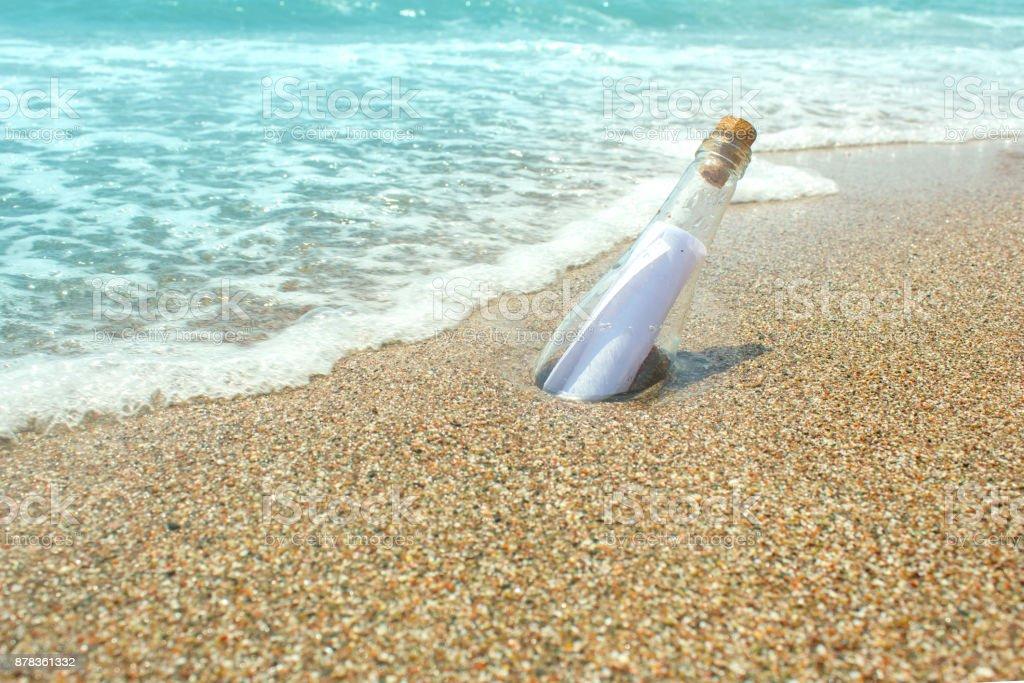 Message dans une bouteille en verre sur le sable. Mer et des vagues. Une note sur le Salut, s'il vous plaît aider - Photo