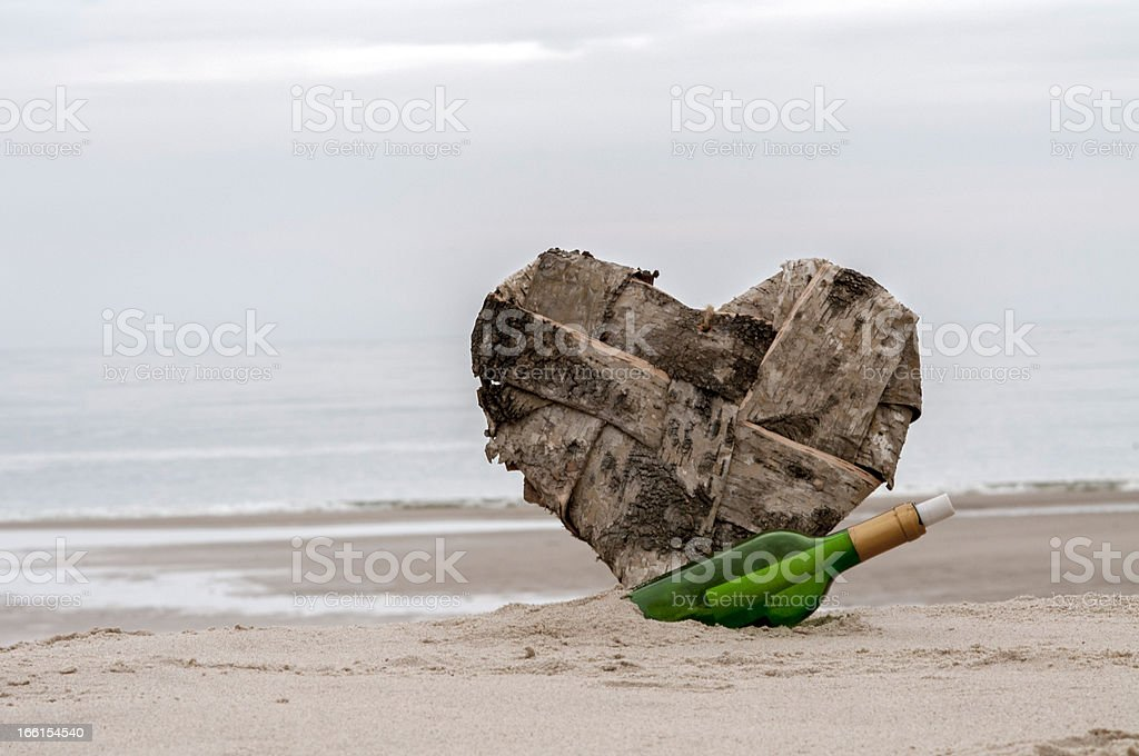 message in  bottle and a lost heart on the beach royalty-free stock photo