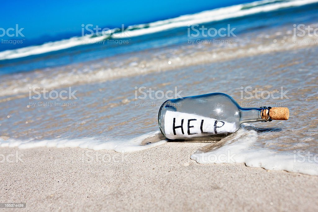 Message in bottle at waters edge says Help! stock photo